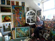 The artist Peter Rodulfo in his studio surrounded by his artwork