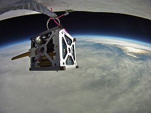 PhoneSat - PhoneSat 1.0 during high-altitude balloon test. The antenna made from yellow tape measure is deployed.