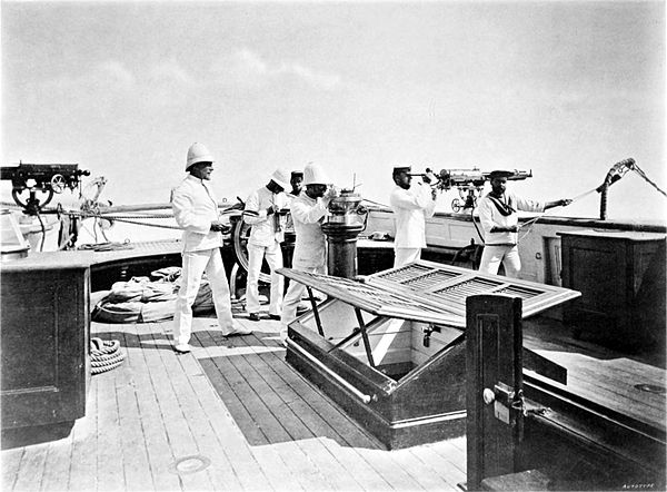Black and white photograph of sailors on the deck of a ship, looking off to the right.