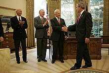 Grey-haired Collins and Armstrong are clapping to the right of Aldrin, as Aldrin shakes hands with the President in the Oval Office. All are dressed in suit and tie. A wood desk is behind Aldrin. Windows and gold drapes fill the background.