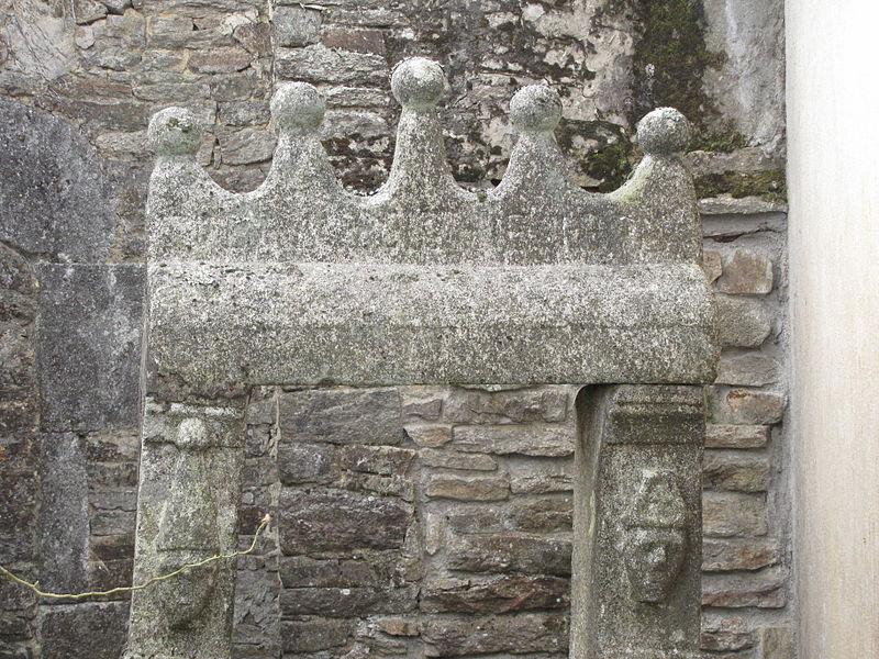 Sur les parements des supports du treuil sont taillées des têtes coiffées de mitres ou bonnets.