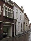 foto van Huis met witgepleisterde eenvoudige empire lijstgevel en ingangsomlijsting, nog geheel woonhuisvorm