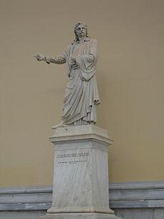 Ο ανδριάντας του Ρήγα Φεραίου, αριστερά της εισόδου του Πανεπιστημίου Αθηνών. Ανεγέρθηκε το1871 με δαπάνη του Γεωργίου Αβέρωφ. Έργο του γλύπτη Ι. Κόσσου.