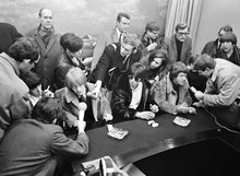 Black and white photo of young white males sat by a long dark desk and surrounded by a crowd of people, including men with microphones attempting to interview them