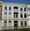 foto van Herenhuis met gepleisterde lijstgevel. Middenpartij met loggia's, stucversieringen en kroonlijst op uitgekraagd boogfries