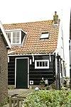 Perceelsgedeelte van een grotendeels houten huis