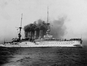 A large white warship belching thick black smoke plows through the water