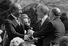 Anwar Sadat, Jimmy Carter, and Menachem Begin shaking hands on the White House grounds