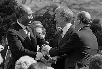 Anwar Sadat - President Jimmy Carter shaking hands with Sadat and Israeli Prime Minister Menachem Begin at the signing of the Egyptian–Israeli Peace Treaty on the grounds of the White House, 1979