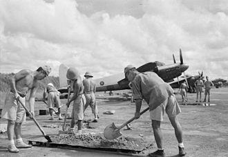War in Vietnam (1945–46) - Japanese POW's under British supervision repairing the taxiing strip at Saigon airfield, with behind them RAF de Havilland Mosquito aircraft, December 1945