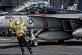 Sailor directs an E-A-18G aboard USS George Washington. (10193352754).jpg
