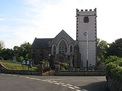 Stone building with white painted square tower. In the foreground is a road junction.