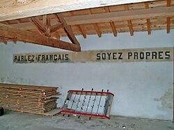 """«Parlez français, soyez propres"""" cartel sobre el muro de una escuela del sur de Francia."""