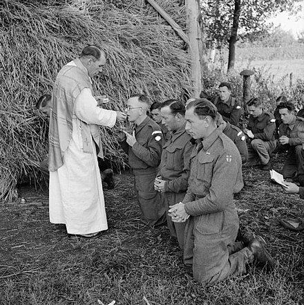 A priest administers Communion during Mass in a Dutch field on the front line in October 1944.