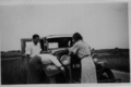 Three people next to car with open hood near Gilleleje, Denmark.png