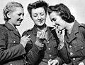 Three women of the British ATS light up a cigarette.jpg