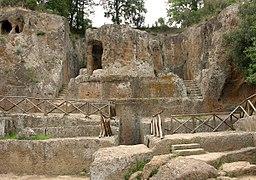Mausolée circulaire en tuf entouré d'escaliers et directement taillés dans la pierre de la colline derrière.