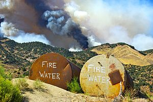 Wildfire suppression - Tanks filled with water await possible use as a fire burns on the crest of a hill in Lebec, California, 2010