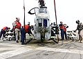 """US Navy 030327-N-5027S-005 Marine Aviation Ordnancemen assigned to the """"Gunrunners"""" of Marine Helicopter Attack-Light Squadron Two Six Nine (HMA-L-269) load an AH-1W Super Cobra aboard the amphibious assault ship US.jpg"""