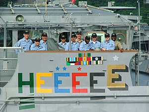 "USS Chancellorsville - Crew members aboard the USS Chancellorsville assemble on the ship's bridge wing to admire the painting of a gold ""Battle E"", signifying the ship as having been awarded the Navy's prestigious Battle Effectiveness Award for five consecutive years."