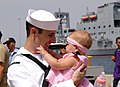 US Navy 090801-N-0327S-027 Fire Controlman 2nd Class Daniel Boes, assigned to the amphibious dock landing ship USS Comstock (LSD 45), holds his daughter for the first time after returning from a scheduled deployment.jpg