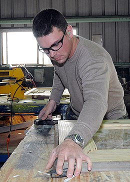 US Navy 100224-N-6357K-005 Builder 3rd Class Greg Lever, from Londonderry, N.H., assigned to Naval Mobile Construction Battalion (NMCB) 7, assembles a picture frame to be used in the refurbished Camp Mitchell chaplain's office