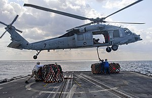 US Navy 120121-N-VY256-068 Sailors aboard the Ticonderoga-class guided-missile cruiser USS Cape St. George (CG 71) attach outgoing mail to an MH-60.jpg