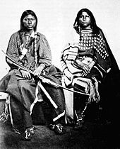 Photograph of a Kiowa couple showing elk teeth on the woman's dress