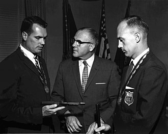 William McMillan (sport shooter) - McMillan (left) and James Enoch Hill (right) are commended by David M. Shoup, Commandant of the Marine Corps. McMillan holds the pistol he used at the 1960 Olympics.