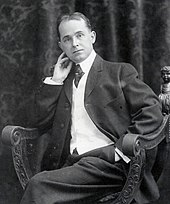 Une photographie en noir et blanc d'un âge moyen assis, l'homme dégarni dans un costume et une cravate, la tête penchée légèrement sur sa main droite