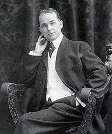 O fotografie alb-negru a unui bărbat de vârstă mijlocie într-un costum care pozează așezat pe un scaun