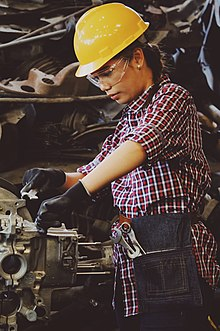 A woman wearing a hard hat and gloves, working on an engine.