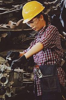 Una mujer con casco y guantes, trabajando en un motor.