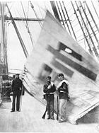 two Mainres instand in front of and one sailor next to a white flag with a Chinese character, displayed from the rigging of a ship