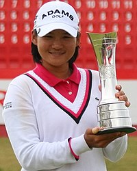 A woman in all white clothing with a red polo golf shirt underneath the sweater and the wrist and neck seems are colored in magenta and blue with a white golf hat with black lettering and a silver metal trophy in hand