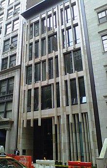 The narrow, six-story facade of a building has white poles going vertically all along its facade.