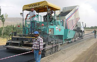 Asphalt concrete - A machine laying asphalt concrete, fed from a dump truck