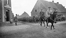 a black and white photograph of a mounted officer leading troops on foot