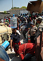 A Haitian woman carries a 5-gallon jug of water on her head amongst other residents collecting relief aid in Petit Place Cazeau, Port-au-Prince, Haiti 100223-N-HX866-003.jpg