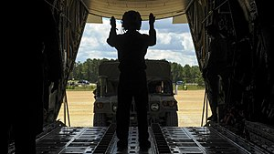 Loadmaster - A Royal Australian Air Force loadmaster directing a vehicle onto a C-130J Hercules in 2016