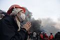 A woman making her prayer right in the middle of raging clashes. Ukraine, Kyiv. Events of February 19, 2014.jpg
