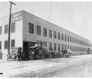 Abbott-Detroit - 7.5x9.5 black and white photograph of the Abbott Motor Company showing a truck and three automobiles next to the building