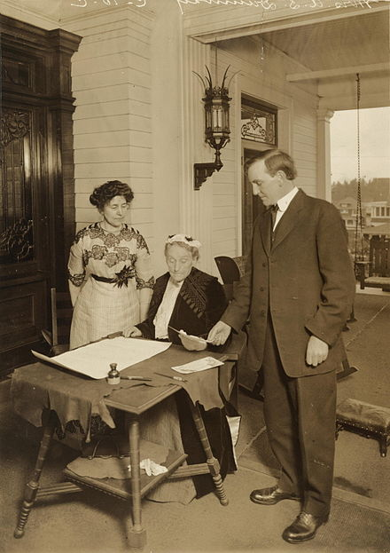 Abigail Scott Duniway (seated) with Governor Oswald West, signing the women's suffrage amendment
