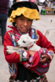 Amerindian girl from Peru holding a baby lamb.png