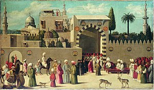 Bustling city scene of men dressed in turbans outside the walls of an Oriental city. An official appears to be holding court at the gate, reclining on a red sofa with two individuals facing him (perhaps parties to a dispute). Others observe the proceedings--many men on foot, two men on camel-back, and one on horse-back. A monkey, a male deer and a female deer are also present in the crowd.