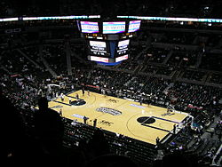 The inside of an arena with large scoreboard visible, which is set up for basketball.