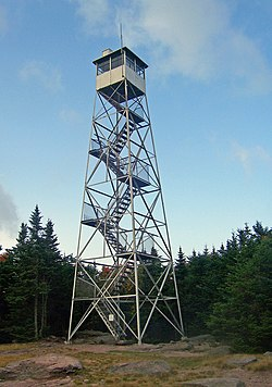 A steel frame tower on a rocky ground with a metal cab on top and stairs up the inside. Behind it are evergreen trees.