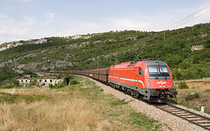 Bank engine - SZ Taurus pushing a freight train on the grade between Koper and Hrpelje-Kozina in Slovenia. An SZ class 363 is leading the train. July 2007.