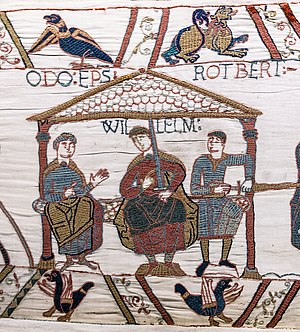 Tapestry image of a seated man in robes holding a sword with WILLELM written above his head flanked by two seated men in chainmail.