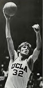 A man, wearing a white jersey with UCLA 32 on front, with both arms raised and ball in his right hand while looking to his left.
